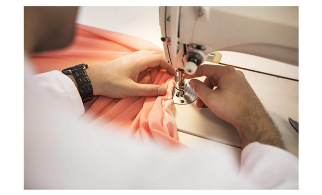 Threading a red dress with a sewing machine